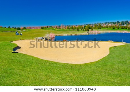 Sand bunker on the golf course with the cart at the background. - stock photo