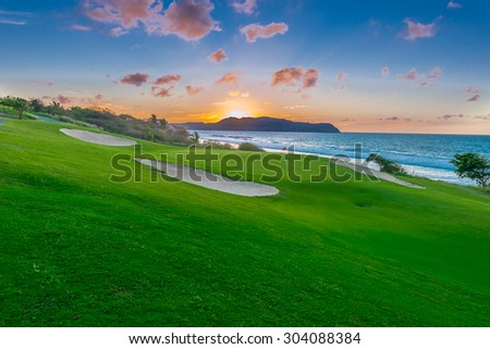 Sand bunkers at the beautiful golf course at the ocean side at sunset, sunrise time. - stock photo