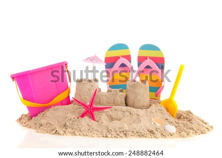 Sand castle and toys at the beach isolated over white background - stock photo