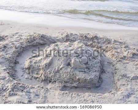 Sand castle built on a beach on sunny day. - stock photo
