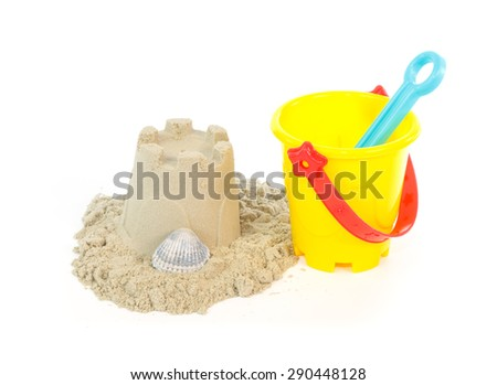 Sand castle built with a yellow toy bucket isolated on a white background - stock photo