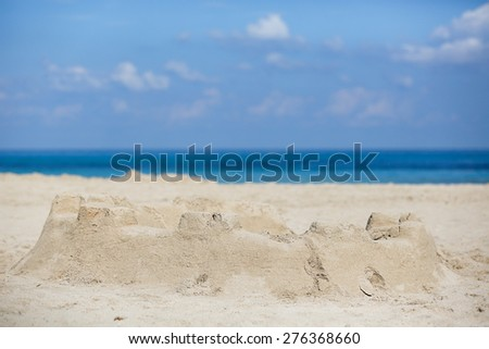 Sand castle on a sandy beach, lit by bright sunlight with cloudscape and deep blue sea in the background. Summer activities and vacation concept.  - stock photo