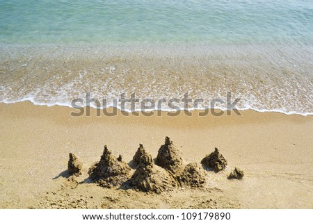 Sand castle on an empty beach with gentle ocean surf - stock photo