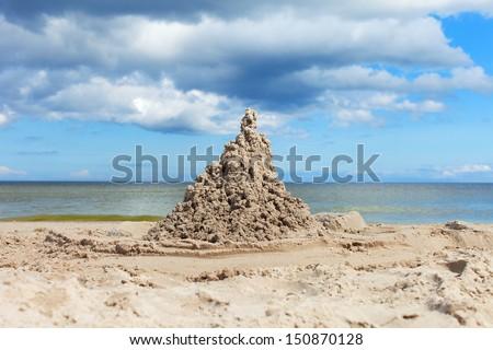 Sand castle on Baltic beach. - stock photo