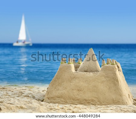 Sand Castle on beach with white boat in ocean background - stock photo
