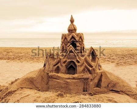 Sand castle on the beach. Vintage retro style - stock photo