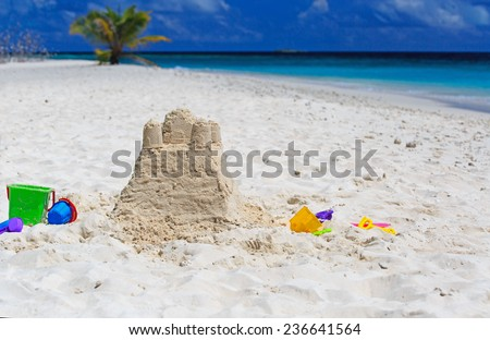 Sand castle on tropical beach and kids toys - stock photo