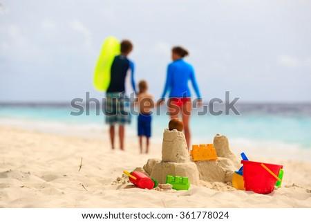 sand castle on tropical beach, family vacation - stock photo