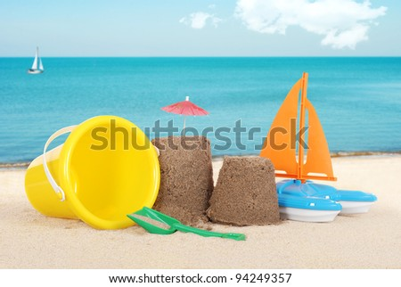 Sand castle with toys - stock photo