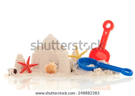 Sand castle with toys isolated over white background