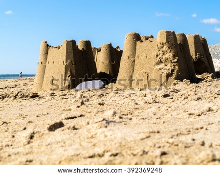 Sand castles found on the beach at Dinas Dinlle in Gwynedd, North Wales UK. It is a sunny day and there is an unrecognisable person and a lightly clouded blue sky in the background. - stock photo