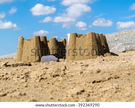 Sand castles found on the beach at Dinas Dinlle in Gwynedd, North Wales UK. It is a sunny day and there is a lightly clouded blue sky in the background. - stock photo