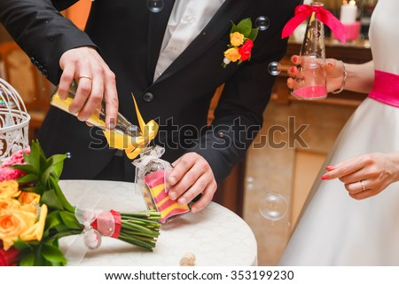 sand ceremony being performed at wedding. Hands of bride holding vase with colorful sand during wedding party - stock photo