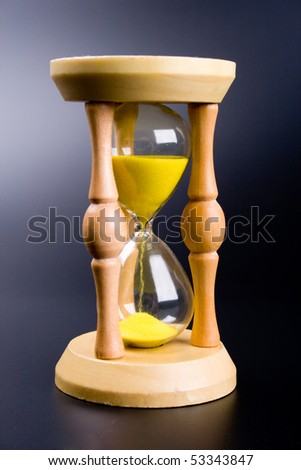 sand clock showing how is time passing on black background - stock photo