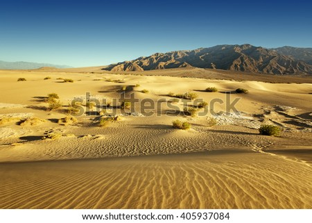 sand desert and rocky mountains in the background - stock photo