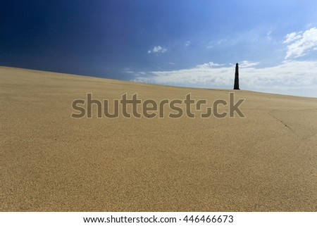 Sand dune near Memory beach from the north of Portugal against blue sky with some interesting light and clouds seeing his iconic granite obelisk