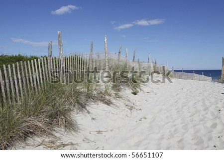 Sand dune with dune grass and worn fence