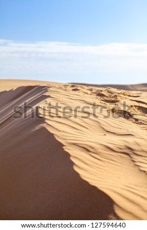 Sand dunes in Sahara desert with blue sky - stock photo