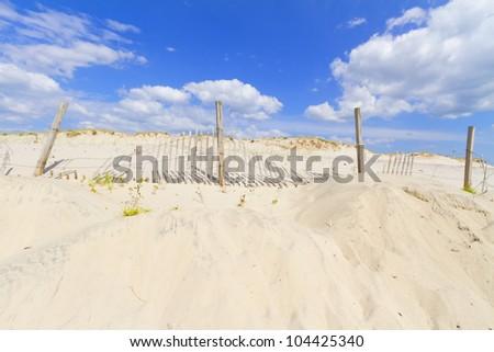 Sand dunes on Atlantic coast with a fence. - stock photo