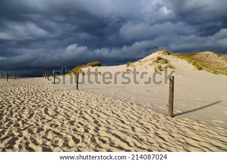 Sand dunes on the Baltic coast in the morning - storm clouds - stock photo