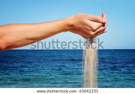 Sand falling from the woman's hand - stock photo