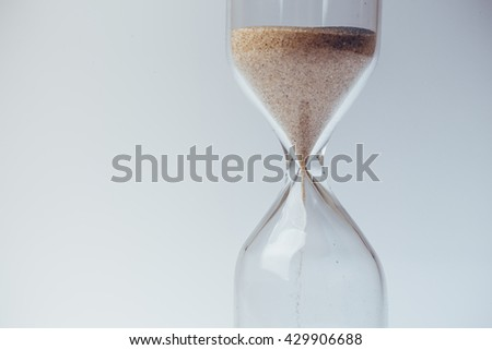 Sand flowing through an hourglass concept for time running out, background - stock photo