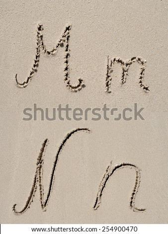 Sand font or letter set group or collection carved on an exotic beach near the sea in summer - stock photo