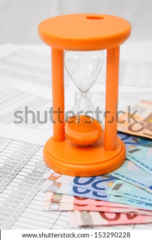 Sand-glass and banknotes on documents. - stock photo