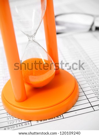 Sand-glass and glasses on documents. - stock photo