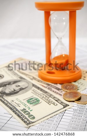 Sand-glass, money on documents. - stock photo