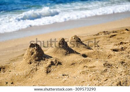 Sand heaps towers on a beach - stock photo