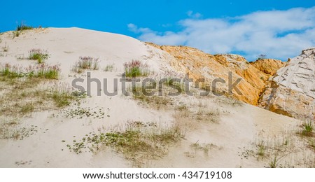 Sand hill with vegetation against the blue sky with clouds. - stock photo