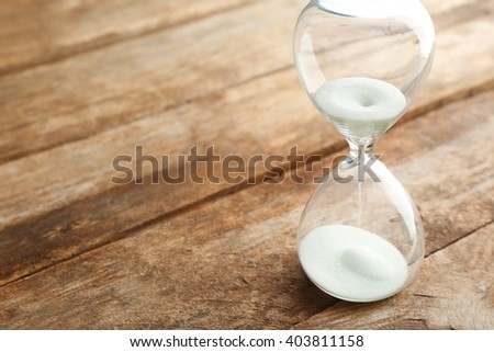 Sand hourglass on wooden background - stock photo