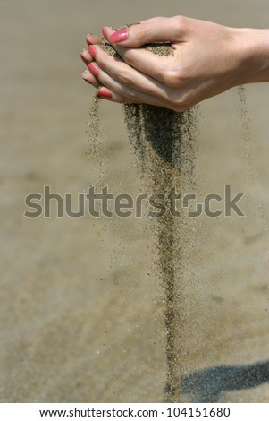 Sand is falling from the girl's hands
