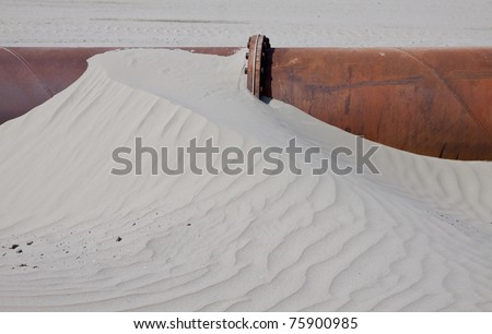 Sand on a dredge pipe - stock photo