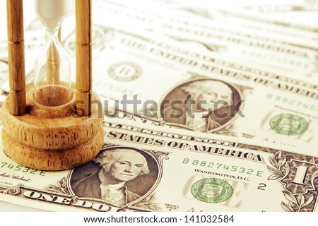 Sand passing through timer on banknotes - stock photo