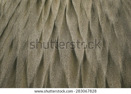 Sand patterns on a beach caused by running water - stock photo