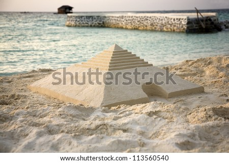 Sand pyramid on the beach - stock photo