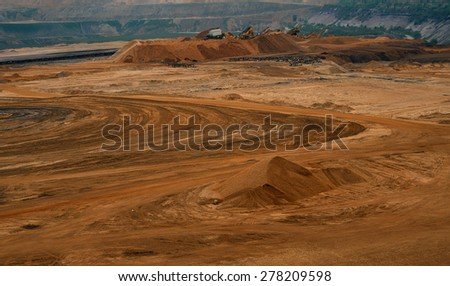 Sand quarry / Brown coal quarry / Bunk wall surface mine with exposed colored minerals and brown coal, mining equipment at the bottom the pit, view from above, top view - stock photo