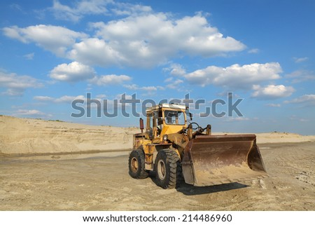 Sand quarry, excavating equipment, bulldozer with heap of sand in background - stock photo