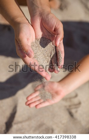 Sand running through female hands into kid's hands.Young woman with sand in her hands playing with a child. Sand as a symbol for time running out.