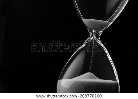 Sand running through the bulbs of an hourglass measuring the passing time in a countdown to a deadline, on a dark background with copyspace - stock photo