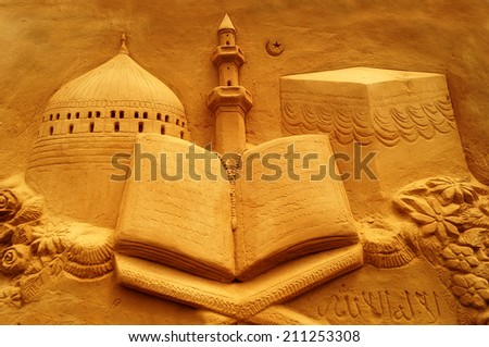 Sand sculpture depicting the muslim tradition of eid or ramzaan/ramadan with mosques,minaret,and the open quran(religious scriptures) and tombstone of their prophet like in mecca - stock photo