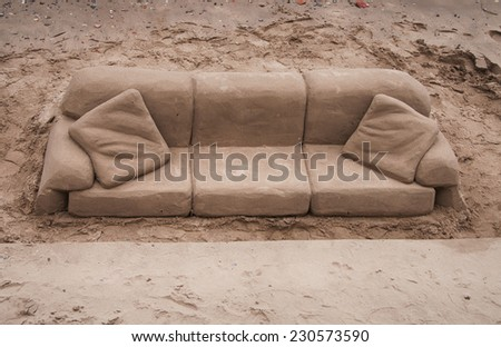 Sand sculpture of a sofa and cushions carved out of golden beach sand on the south bank of the River Tames, London, England - stock photo