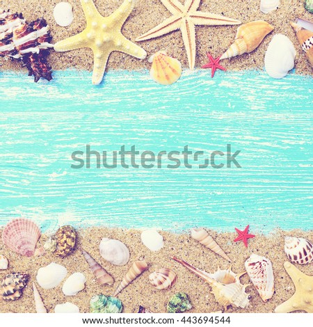 Sand, seashells and starfish on a blue wooden background. Photo in vintage style - stock photo