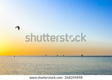 Sand spit in the blue sea and people silhouettes on a background picturesque sunset in the summer evening - stock photo
