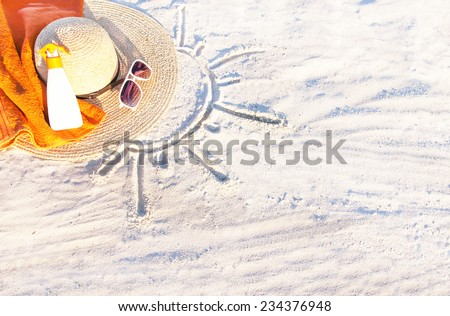 Sand texture (background) with hat, towel, sunscreen (suncream), sunglasses on the beach. The sun drawing in the sand. The empty pattern for  message. Summer vacations concept. Copy space.  - stock photo