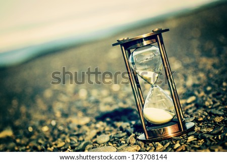 Sand Timer on Pebble Beach - Hourglass on stony beach, with an instagram effect. - stock photo