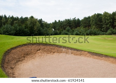 Sand trap and putting green with flag at golf course - stock photo
