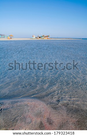 Sand with red fragments from sea urchin shells, limpid blue water and distant sun umbrellas on Elafonissos beach in south-west Crete, Greece. The beach is a protected scientific area - stock photo